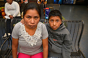 Tucson, Arizona, USA, June 26, 2014: A Guatemalan woman, (left), and her 10-year-old son wait in Tucson at bus station where they were dropped off by the U.S. Border Patrol after being apprehended near Douglas, Arizona, USA, where they crossed the border illegally from Mexico.  The two traveled for about five days from Guatemala to get to the Arizona border.  They, along with others, heard in Guatemala that mothers with children could find work in the U.S. and better their lives.  Recently flooded with undocumented migrants from Central America, federal authorities are transporting children with adults to bus stations where they will head to other states in the U.S.  Their status in the U.S. will be addressed by authorities after they reach their destination.  The boy translated Mayan Q'anjob'al (also Kanjobal) into Spanish for his mother, who spoke only her native language.