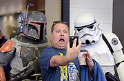 Shane Donovan of Ottawa takes a selfie with Boba Fett  and a Stormtrooper during the 43rd Antique Collectible Toy and Doll Show Sunday at the Kane County Fair grounds.