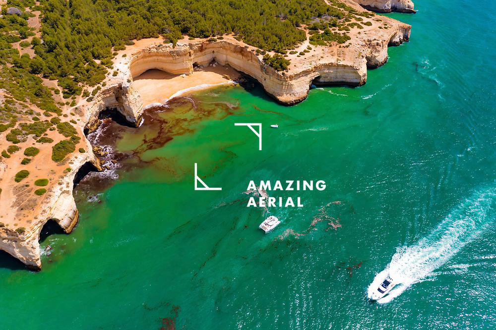 Aerial view of a boat, catamaran and a yacht cruising along the sea near the cliffs of Praia da Corredoura beach in Lagoa, Algarve, Portugal.
