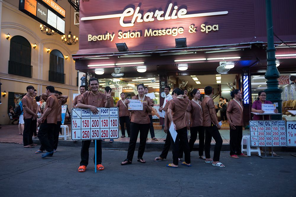 As evening falls on the city, employees of a massage salon promote their business and look for customers on Khao San Road in Bangkok, Thailand.  (June 2017)