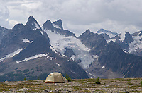 Tent at backcountry camp on Rocky Point Ridge. Northern peaks of Bugaboo Provincial Park in the distance, Purcell Mountains British Columbia.