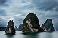 Halong Bay is seen under stormy clouds. The limestone formations, said to be the back of a dragon that plunged into the bay, are among 3,000 such formations in this UNESCO World Heritage site. Robert Dodge, a Washington DC photographer and writer, has been working on his Vietnam 40 Years Later project since 2005. The project has taken him throughout Vietnam, including Hanoi, Ho Chi Minh City (Saigon), Nha Trang, Mue Nie, Phan Thiet, the Mekong, Sapa, Ninh Binh and the Perfume Pagoda. His images capture scenes and people from women in conical hats planting rice along the Red River in the north to men and women working in the floating markets on the Mekong River and its tributaries. Robert's project also captures the traditions of ancient Asia in the rural markets, Buddhist Monasteries and the celebrations around Tet, the Lunar New Year. Also to be found are images of the emerging modern Vietnam, such as young people eating and drinking and embracing the fashions and music of the west. His book. Vietnam 40 Years Later, was published March 2014 by Damiani Editore of Italy.