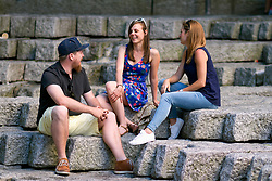Friends sitting on steps in urban area chatting and smiling