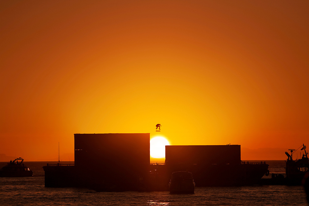 Sun Jump<br /><br />Skateboarder Ryan Descenzo had the idea of building a gap between two shipping containers, so in order to make it a bit more dramatic we decided to place the containers on a barge and drag it with a tug boat out into the ocean. It wasn't until the sun was about to set that he landed this nollie heelflip over the gap (and sun) in English Bay, Vancouver, Canada.