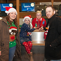 Leona Daly and Martin Caulfield with their daughter Casey Daly-Caulfield checking in for their Santa's Flight with Swissport's Laura Wesrzyn