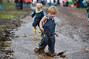 Boys playing ina puddle left by the heavy rain which created a mud bath at Glastonbury Festival 2016, United Kingdom. Glastonbury Festival is the largest greenfield festival in the world, and is now attended by around 175,000 people. Its a five-day music festival that takes place near Pilton, Somerset. In addition to contemporary music, the festival hosts dance, comedy, theatre, circus, cabaret, and other arts. Held at Worthy Farm in Pilton, leading pop and rock artists have headlined, alongside thousands of others appearing on smaller stages and performance areas.