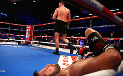 Sam Sexton (centre) on the floor during the Heavyweight title contest at The Macron Stadium, Bolton.
