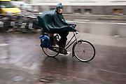 Fietsers rijden door de regen.<br /> <br /> Cyclists are riding in the rain.