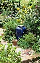 Looking up the garden from the patio. Empty blue glazed pot as focal point