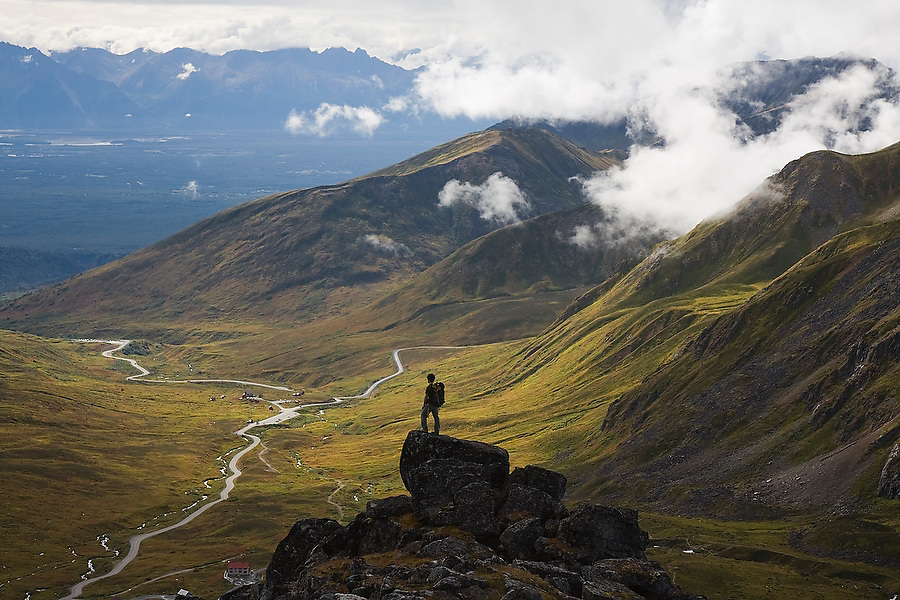 Hiker Craig Weilands stands on a rock outcrop looking down at the Independence Mine State Historical Park and the Matanuska Valley from the Talkeetna Mountains near Hatcher Pass, Alaska.