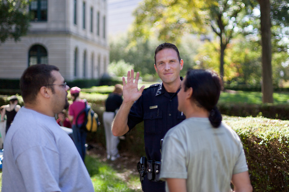 A CMPD officer waves at the camera as he discusses the days events with two Occupy Charlotte demonstrators.