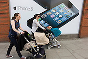 Two mothers pushing their baby's buggies, walk past a large poster for the iPhone 5 on the wall of a Carphone Warehouse retailer.