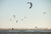 Kite boarder walks his kite as a cargo ship passes on Sullivan's Island, SC.