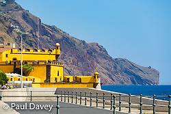 The ochre walls of a former fort, now restaurant, contrast with the rugged cliffs of Madeira near Funchal. MADEIRA, September 26 2018. © Paul Davey
