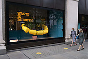 Two women wearing facial coverings walk past the latest window of Selfridges featuring a theme about plastic waste, on 26th August 2020, in London, England. Selfridges latest green theme is called Project Earth, a 'transformational' sustainability initiative with ambitions to change the way consumers shop, helping to reduce waste, choose 'forest friendly' products and chose recycled or 'pre-loved' products.