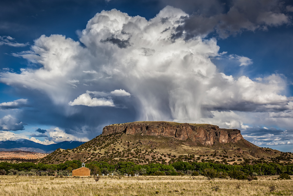 Dramatic storm clouds seemingly erupt from Black Mesa near the old church and cemetery at San Ildefonso Pueblo, New Mexico.