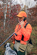 Upland hunter talking on a cell phone while afield.
