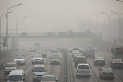 Traffic move through the thick haze in Beijing, China, on Monday, Nov. 30, 2015.  China has made a concerted effort to cut down pollution, especially in the nation capital, however there are still heavily polluted days especially in the winter months.