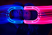 A young couple is framed by a glowing pair of magnets.Black light