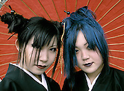 Two young Harajuku cosplay girls wearing traditional Kimono and holding a Japanese red, paper umbrella. Harajuku, Tokyo Japan September 2005