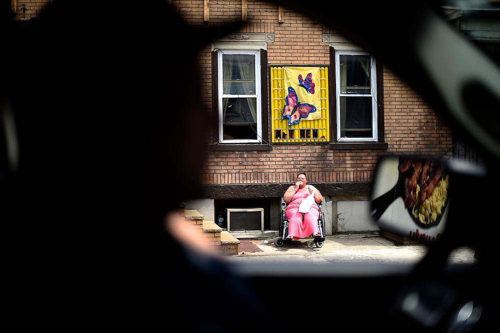 A woman eats a donut, as a truck transporting breakfast food is reflected in the driver's side mirror, in Shamokin, PA, a town of 7,000 in coal country, on May 1, 2014.  The city is over $800,000 in debt and even had the gas temporarily turned off in city hall.  Long prosperous from the coal industry, in the 1980s there were 3 movie theaters, 3 dress shops, 3 shoe shops, 2 five and dime stores, and a skating rink, but none remain.