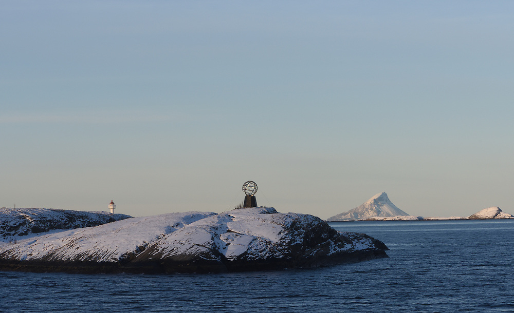 The Arctic Circle 66° 33' north is marked by a globe on the islet of Vikingen between Nesna and Ørnes. The monument is seen on Hurtigruten voyages. The island of Hestmona and the mountain Ambota are in the background.  Vikingen, Rødøy, Nordland, Norway.