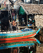 A fisherman untangles his nets in the floating village of Kompong Phluk on the great Tonlé Sap lake, Cambodia