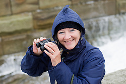 Attractive older woman with binoculars at  whitby