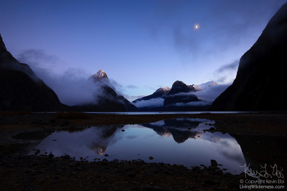 Mitre Peak, Mount Pembroke, and other mountains in Fiordland National Park are reflected in a tidepool next to Milford Sound, New Zealand, on a foggy morning just before sunrise.