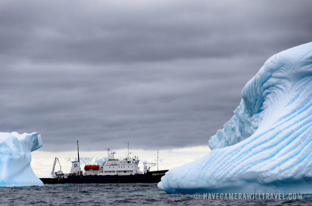 The Polar Pioneer, and Antarctic cruise ship operated by Aurora Expeditions, idles in the distance behind two ornately carved blue icebergs near Two Hummock Island on the Antarctic Peninsula.