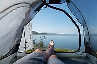 Legs of male backpacker in tent with view over lake Virihaure from Staloluokta, Padjelantaleden Trail, Padjelanta national park, Sweden