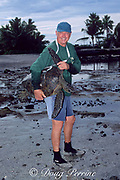Marc Rice, with HPA/NMFS sea turtle research, carries green sea turtle, Chelonia mydas, back to water for release after study, Kaloko-Honokohau National Historical Park, Kona, Hawaii ( Pacific Ocean )