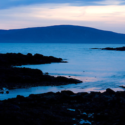 The sun sets behind Cadillac Mountain as seen from a cove on the Schoodic Peninsula in Maine's Acadia National Park.