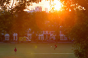 During the UKs Coronavirus lockdown, the May Bank Holiday brought warm temperatures for Londoners who stayed late in their local green space and as the sun sets over residential roofs, a person throws a frisbee in Ruskin Park, in Lambeth, on 24th May 2020, in London, England.
