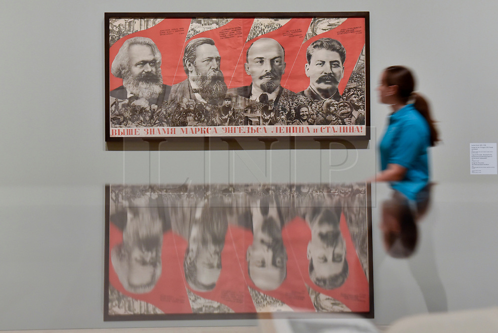 """© Licensed to London News Pictures. 07/11/2017. London, UK.  A student from Thomas Tallis School, Kidbrooke, south London, walks by """"Under the Banner of Marx, Engels, Lenin and Stalin!"""", 1933, by Gustav Klutsis, at a preview of """"Red Star Over Russia: A Revolution in Visual Culture 1905-55"""" at Tate Modern.  The exhibition marks the centenary of the October Revolution and presents the visual history of Russia and the Soviet Union with works drawn from the late graphic designer David King. Photo credit: Stephen Chung/LNP"""