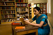 """Ganga Thampi, a classical Indian dance teacher in a quiet moment of study  at the highly prestigious Kalakshetra school for the arts, Chennai. The school was founded in 1936 and due to its exacting and demanding schedule is considered India's formost classical dance academy of this ancient cultural art heritage that is informally known as """"temple dancing"""" and that dates back to the Natya Shastra, the 2000 year old text that lays down the principles of Indian dramatic theory and performance. Tamil Nadu, India."""