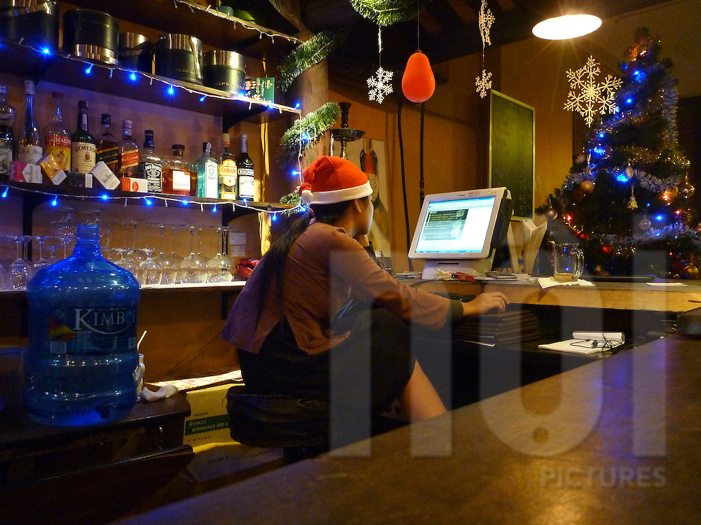 A bartender girl wearing a Santa Claus hat is playing video games on the cashier machine of the bar, near a christmas tree in Hanoi, Vietnam.