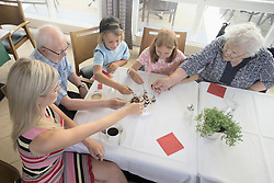 Grandparents eating flan cake with grandchildren and daughter in rest home, Eichenau, Bavaria, Germany