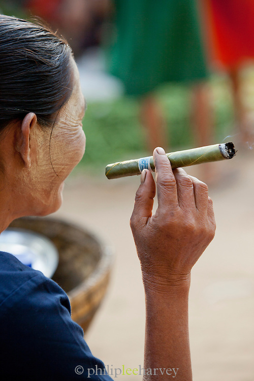 A seller smokes a cheroot, a local cigar, at the morning market in Bagan new town in Myanmar