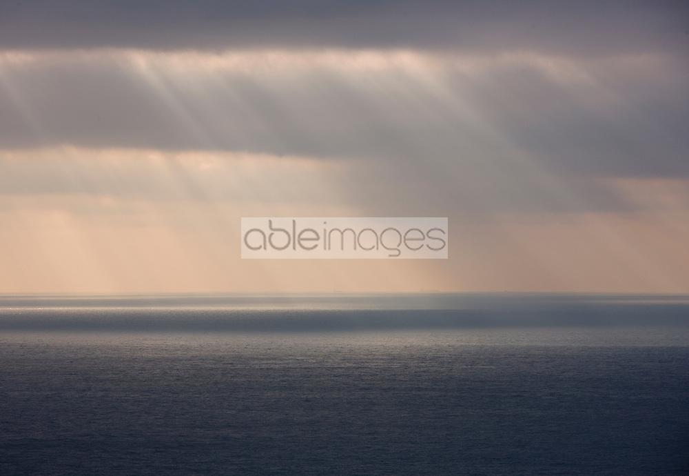 Grey sky with rain and sun rays shining on the ocean
