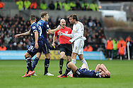 Swansea city's Michu (9) has words with Michael Dawson after he collides with Tottenham's Scott Parker (on ground) and is booked by referee Anthony Taylor (c) . Barclays Premier League, Swansea city v Tottenham Hotspur at the Liberty Stadium in Swansea, South Wales on Saturday 30th March 2013. pic by Andrew Orchard, Andrew Orchard sports photography,
