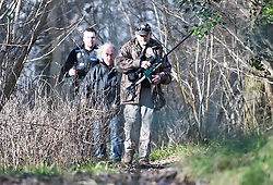 © Licensed to London News Pictures. 18/01/2018. Curridge, UK.  A man carrying a tranquilliser rifle and a police officer search through woodland at the scene in Curridge, Berkshire where police are hunting for a wolf that has escaped from its enclosure at the UK Wolf Conservation Trust nearby. Armed police are on the scene. Photo credit: Ben Cawthra/LNP