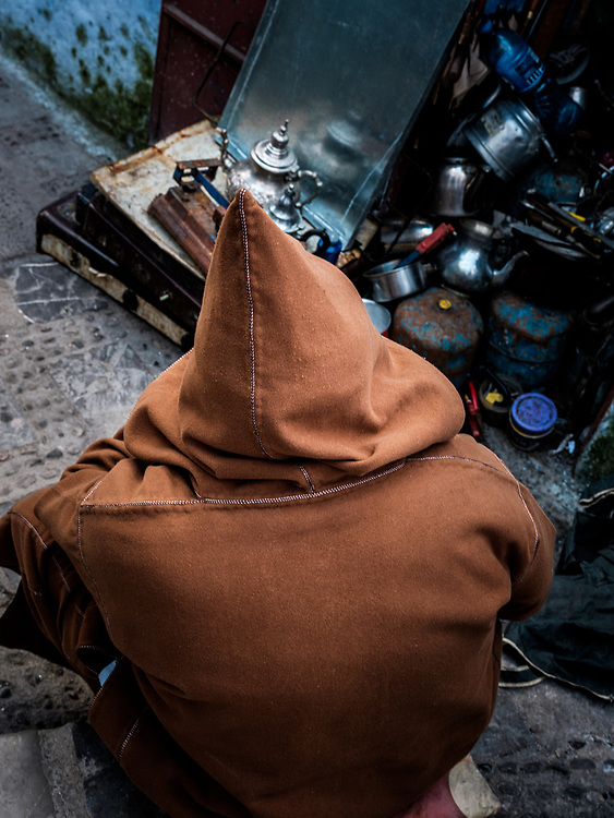 CHEFCHAOUEN, MOROCCO - CIRCA MAY 2018:  Moroccan man wearing a typical djellaba seating on the medina in Chefchaouen