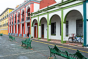 Brightly painted colonnaded style buildings in Tlacotalpan, Veracruz, Mexico. The tiny town is painted a riot of colors and features well preserved colonial Caribbean architectural style dating from the mid-16th-century.