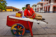 """09 JANUARY 2007 - GRANADA, NICARAGUA: A """"raspado"""" vendor rests on his cart on the plaza in Granada, Nicaragua. Raspados are water and fruit juice served on shaved ice. Granada, founded in 1524, is one of the oldest cities in the Americas. Granada was relatively untouched by either the Nicaraguan revolution or the Contra War, so its colonial architecture survived relatively unscathed. It has emerged as the heart of Nicaragua's tourism revival.  Photo by Jack Kurtz"""