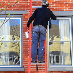 A man on a ladder paints a window frame.