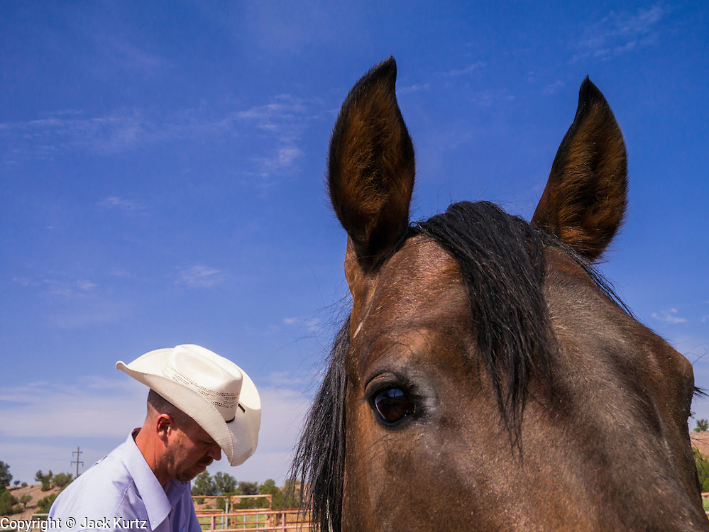 """14 JULY 2012 - FT DEFIANCE, AZ:  A man works with a horse during a horsemanship clinic at the 23rd annual Navajo Nation Camp Meeting in Ft. Defiance, north of Window Rock, AZ, on the Navajo reservation. Preachers from across the Navajo Nation, and the western US, come to Navajo Nation Camp Meeting to preach an evangelical form of Christianity. Evangelical Christians make up a growing part of the reservation - there are now more than a hundred camp meetings and tent revivals on the reservation every year. The camp meeting in Ft. Defiance draws nearly 200 people each night of its six day run. Many of the attendees convert to evangelical Christianity from traditional Navajo beliefs, Catholicism or Mormonism. """"Camp meetings"""" are a form of Protestant Christian religious services originating in Britain and once common in rural parts of the United States. People would travel a great distance to a particular site to camp out, listen to itinerant preachers, and pray. This suited the rural life, before cars and highways were common, because rural areas often lacked traditional churches.   PHOTO BY JACK KURTZ"""