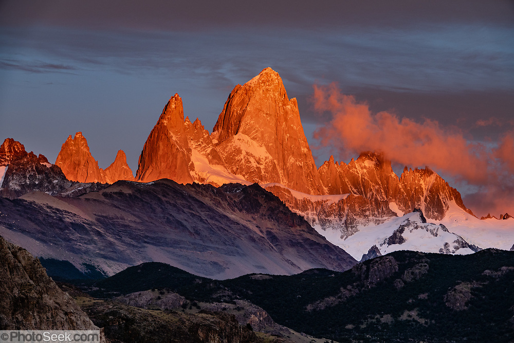 """Sunrise illuminates Cerro Fitz Roy (3405 meters or 11,171 feet elevation), as seen from Mirador al Chaltén on Ruta 23 just 2 km southeast of the village of El Chalten in Santa Cruz Province, Argentina, Patagonia, South America. Monte Fitz Roy is also known as Cerro Chaltén, Cerro Fitz Roy, or Mount Fitz Roy. The first Europeans recorded as seeing Mount Fitz Roy were the Spanish explorer Antonio de Viedma and his companions, who in 1783 reached the shores of Viedma Lake. In 1877, Argentine explorer Francisco Moreno saw the mountain and named it Fitz Roy in honour of Robert FitzRoy who, as captain of HMS Beagle, had travelled up the Santa Cruz River in 1834 and charted large parts of the Patagonian coast. Mt Fitz Roy was first climbed in 1952. Cerro is a Spanish word meaning hill, while Chaltén comes from a Tehuelche word meaning """"smoking mountain"""", due to clouds that usually form around the peak."""