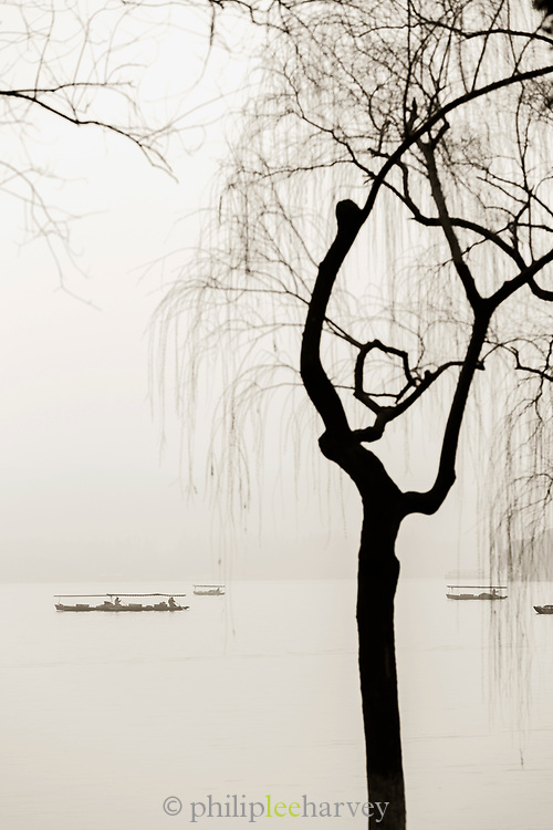 Black and white landscape with view of silhouetted trees, boats and lake at dawn, West Lake, Hangzhou, Zhejiang Province, China