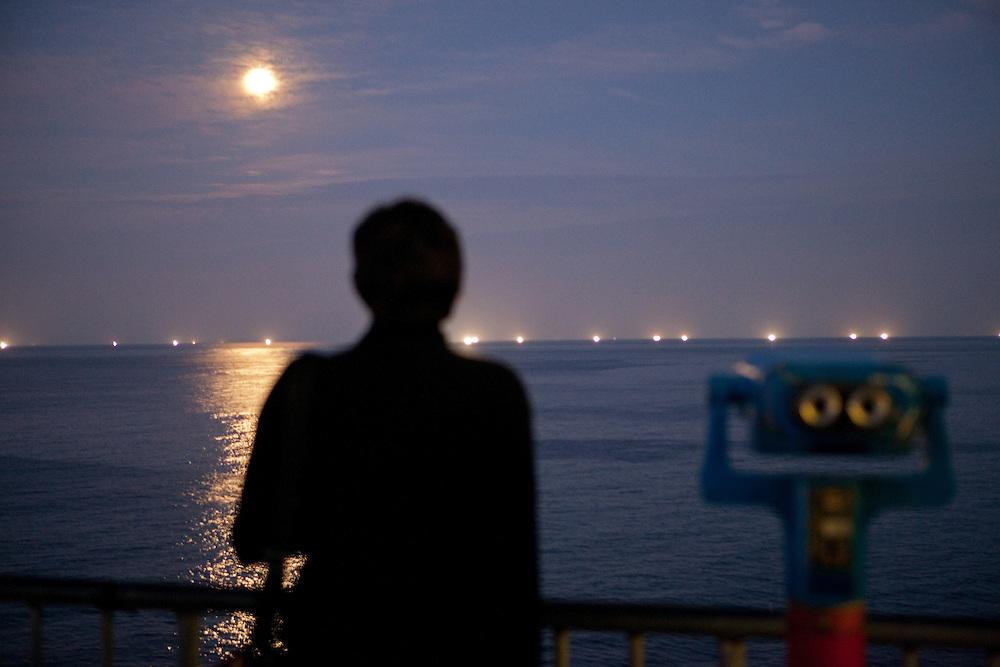 Silhouette of the women beside binoculars looking at the sea in full moon light / Mangyang rest area, South Korea, Republic of Korea, KOR, 04 October 2009.